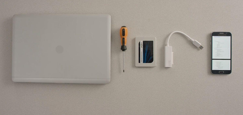 노트북, Crucial SSD, 드라이버 및 컴퓨터 사용 설명서를 책상 위에 펼쳐 놓기