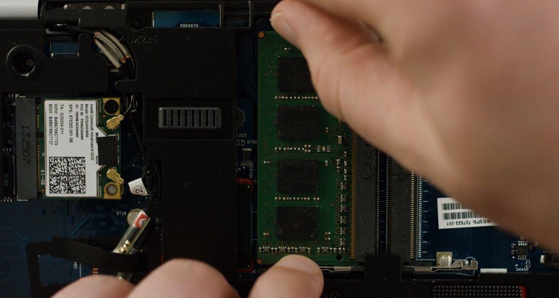 노트북 내부에서 손으로 RAM 메모리 모듈의 클립을 푸는 장면