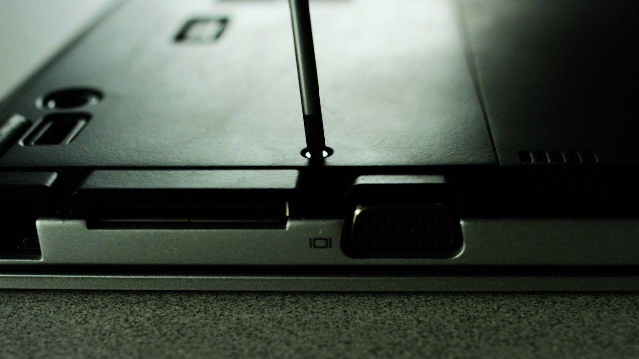 스크류드라이버로 노트북 뒷면에서 나사를 제거하는 장면
