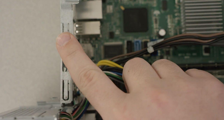 손가락 정전기를 방전시키기 위해 컴퓨터 내부의 도색되지 않은 금속 표면을 만지는 장면